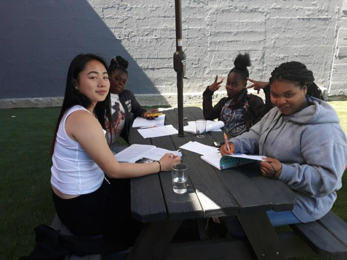 Four girls sitting around a table outside, working on their media projects