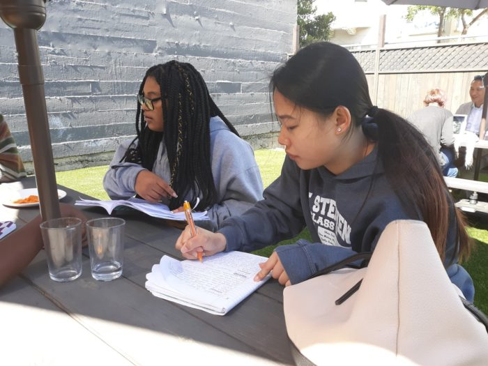 Two girls work on their media projects outside