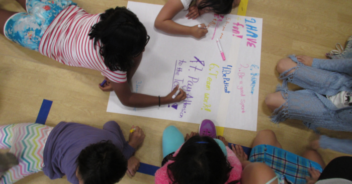 Image: A group of girls of color writing on a large piece of poster paper