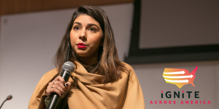 Photo of Zunera Ahmed wearing a camel-colored shawl and speaking into a mic, logo of IGNITE in the bottom right corner