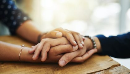 a pair of hands holds another hand in support